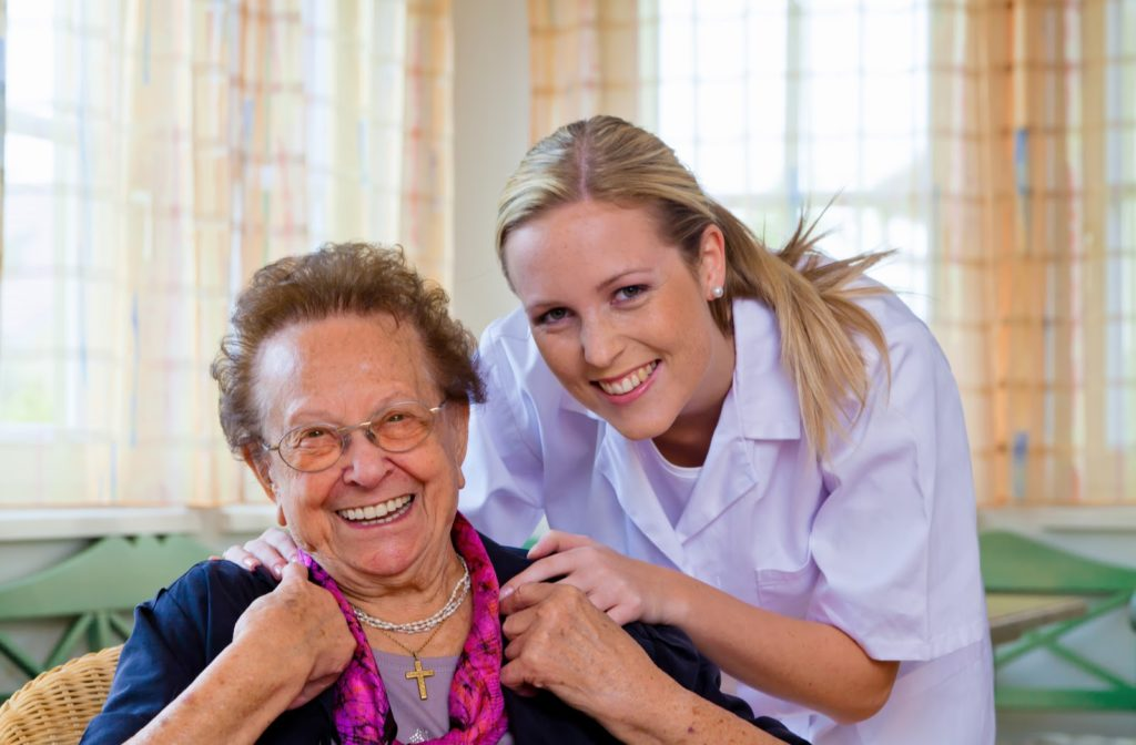 Happy nurse and senior women smiling at senior community